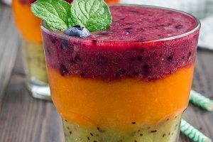Triple smoothie in glass: kiwi-mint, mandarin-apricot and strawberry-blueberry, vertical