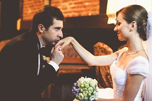 Handsome groom kisses bride's hand