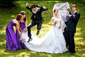 Groom jumps over bride's dress