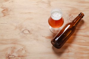 Beer glass and bottle on wood