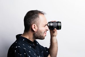 Bearded man looking through lens