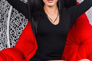 Girl brunette in a black dress sitting on a red cushion in a wicker white chair