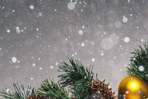 New Year's gift, toy, card, cones. New Year composition on gray concrete background. Snowflakes in the foreground.