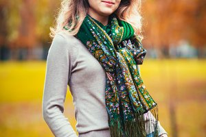 Portrait of a young girl with green neck scarf on the background autumn park