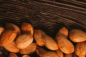 Apricot kernels are scattered on the wooden background