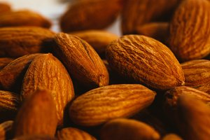 handful of almonds on a white wooden background