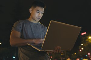 Asian young man with laptop.