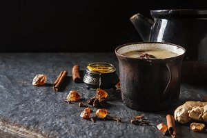 Traditional Indian masala tea in ceramic cup with spices to milk. Dark batskground.