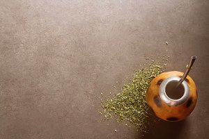 Traditional South American yerba mate tea in the calabash circle and Bombilla. Dark background. Top view