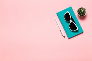Creative flat lay photo of workspace desk with aquamarine notebook, eyeglasses, cactus with copy space pink background, minimal style
