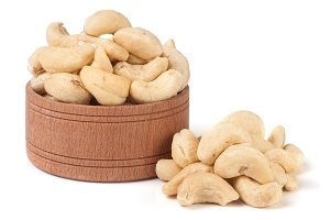 cashew nuts in a wooden bowl isolated on white background