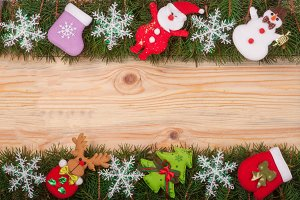 Christmas frame made of fir branches decorated with snowflakes Snowman and Santa Claus on a light wooden background
