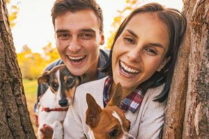 Portrait of happy young couple with dogs outdoors in autumn park looking out from from tree