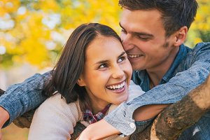 Portrait of smiling young couple outdoors in autumn having fun time