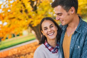 smiling young couple outdoors in park in autumn