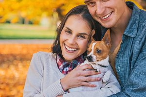 Portrait of happy young couple with dog outdoors in autumn