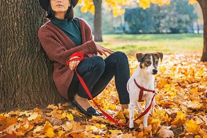 Thoughtful young woman with dog outdoors in autumn