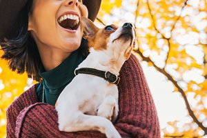 Closeup on happy young woman with dog outdoors in autumn lookin