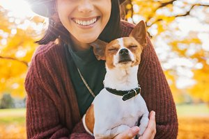 Closeup on happy young woman with dog outdoors in autumn
