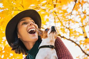 happy young woman with dog outdoors in autumn lookin