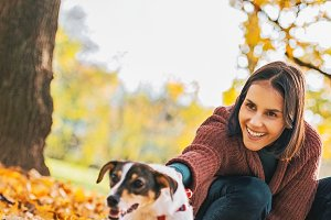 Happy young woman holding cheerful dog outdoors in autumn