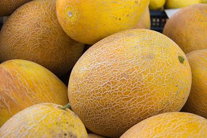 heap of yellow ripe melon on a market counter