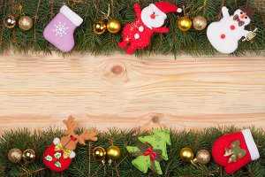 Christmas frame made of fir branches decorated with golden balls Snowman and Santa Claus on a light wooden background