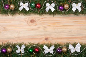 Christmas frame made of fir branches decorated with white bows beads and balls on a light wooden background