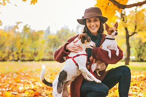 Young woman with two dogs playing outside in autumn leaves