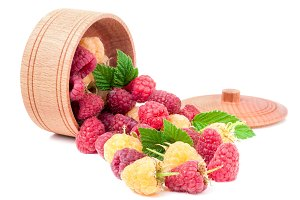 red and yellow raspberries in wooden bowl isolated on white