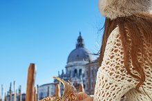 Closeup on Venetian mask in hand of woman in Venice, Italy