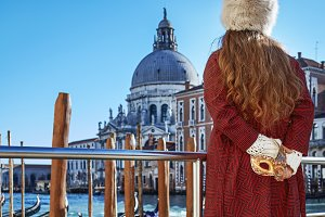 woman on embankment in Venice, Italy holding Venetian mask