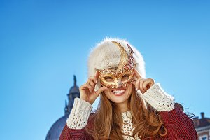 happy young woman in Venice, Italy wearing Venetian mask