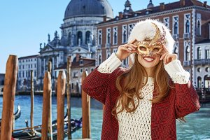smiling elegant woman in Venice, Italy wearing Venetian mask