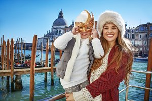 mother and child tourists in Venice wearing Venetian mask