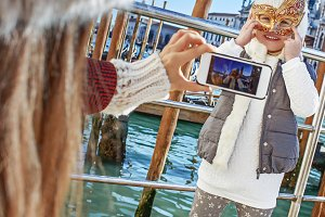 mother taking photo of child wearing Venetian mask, Venice