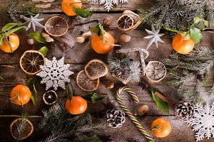 Fairy Christmas background - vintage wood, birdhouse, cinnamon, star anise, oranges, cones, snow. New Year. Top view, blank space