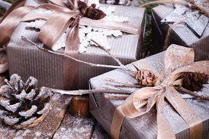 Gift boxes on old wooden background with silver stars, cones, hazelnut, anise, tape, ribbon, snowflakes.