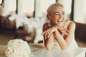 Bride laugh broad sitting at a piano