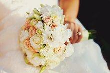 Bride's hand holds a wedding bouquet