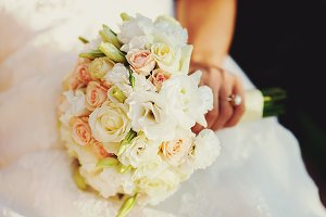 Bride's hand holds a wedding bouquet