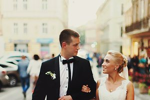 Happy newlyweds walk along old city