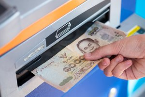 Hand picking banknote from ATM