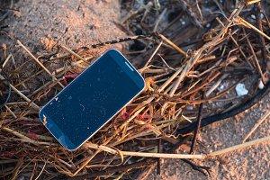 Drown smart phone on the beach
