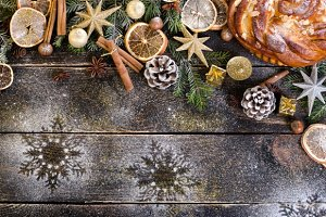 Christmas background - cake, stars, dry oranges, anise, cane, cinnamon on dark wood. Free space for your text.
