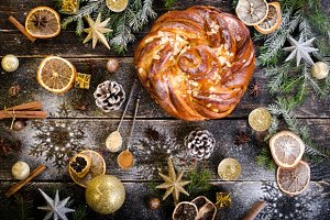 Christmas background - cake, stars, dry oranges, candles, teaspoons with spices, anise, cane, cinnamon on dark wood.