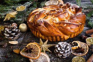 Christmas background - cake, stars, dry oranges, anise, cane, cinnamon on dark wood.