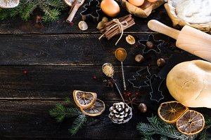 New year baking background - cones, fir tree, dough, flour, rolling pin, eggs, egg yolksover, spices, dry oranges, old dark wood background.