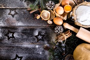 Christmas background - cones, fir tree, dough, flour, rolling pin, eggs, egg yolksover, spices, dry oranges, old dark wood background.