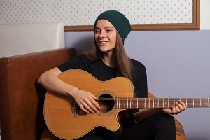 Woman hipster playing on guitar